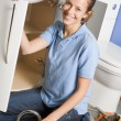 Plumber working on sink smiling — Stock Photo