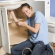 Plumber working on sink smiling - Stockfoto