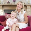 Stock Photo: Mother in living room with baby smiling