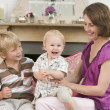 Mother in living room with baby and young boy smiling — Stock Photo #4770574