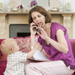 Mother using telephone in living room with baby frowning - Stock Photo