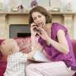 Stock Photo: Mother using telephone in living room with baby frowning