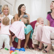 Three mothers in living room with coffee and babies smiling - Stock Photo