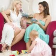 Two mothers in living room with babies and coffee smiling — Stock Photo #4770582