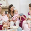 Three mothers in living room with babies and coffee smiling - Photo