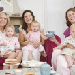 Three mothers in living room with babies and coffee smiling - Stock Photo