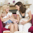 Two mothers in living room with baby and cake smiling — Stock Photo
