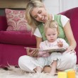 Mother in living room reading book with baby smiling — Stock Photo