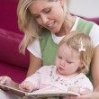 Stock Photo: Mother in living room reading book with baby smiling