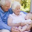 Grandparents outdoors on patio with baby smiling - Foto Stock