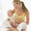 Mother and baby sitting indoors smiling — Stock Photo
