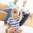 Couple in living room with baby smiling — Stock Photo