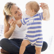 Stock Photo: Mother and baby indoors playing and smiling