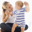 Mother and baby indoors playing and smiling — Stock Photo