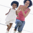 Mother and daughter indoors playing and smiling — Stock Photo