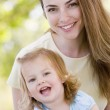 Mother holding daughter outdoors smiling — Stock Photo #4770726
