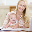 Mother and baby in dining room with laptop smiling — Stock Photo