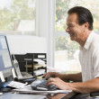 Man in home office at computer smiling — Stock Photo