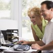 Couple in home office at computer smiling - Stock Photo