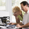 Couple in home office at computer frowning - Stock Photo