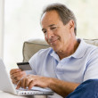 Man in living room with laptop and credit card smiling — Stock Photo
