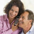 Couple indoors using telephone smiling — Stock Photo