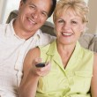 Couple in living room using remote control smiling — Stockfoto
