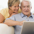 Couple in living room with laptop smiling — Stock Photo