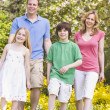 Family walking outdoors smiling — Stock Photo
