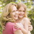 Mother holding daughter outdoors smiling — Stok Fotoğraf #4770896