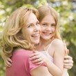 Foto Stock: Mother holding daughter outdoors smiling