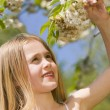Young girl standing outdoors holding blossom smiling - Stock Photo