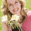 Woman outdoors holding flowers smiling — Stock Photo #4770910