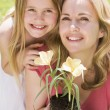 Mother and daughter outdoors holding flower smiling — Stock Photo