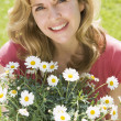 Woman outdoors holding flowers smiling — Stock Photo #4770915