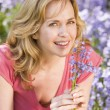 Woman outdoors holding flowers smiling - Stock Photo