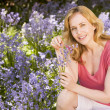 Woman outdoors holding flowers smiling — Stock Photo #4770922