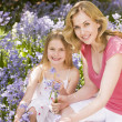Mother and daughter outdoors holding flowers smiling — Stock Photo #4770924