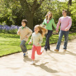 Family running on path holding hands smiling — Stock Photo #4770927