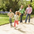 Stock Photo: Family running on path holding hands smiling