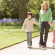 Mother and two young children walking on path holding hands smil — Stock Photo #4770936