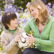 Mother and son outdoors holding ball smiling — Stock Photo