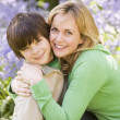 Stock Photo: Mother and son outdoors embracing and smiling