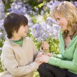 Mother and son outdoors holding flowers smiling — Стоковое фото