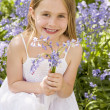 Young girl outdoors holding flowers smiling — Stock Photo