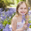 Stock Photo: Young girl outdoors holding flowers smiling