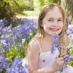 chica joven afuera sosteniendo flores sonriendo — Foto de Stock