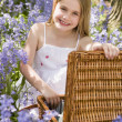 Young girl sitting outdoors with picnic basket smiling - Stock fotografie