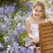 Young girl sitting outdoors with picnic basket smiling — Stock Photo