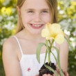 Stock Photo: Young girl outdoors holding flower smiling